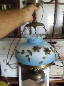 Antique brass chandelier with blue glass globe retrieved from a hundred year old home